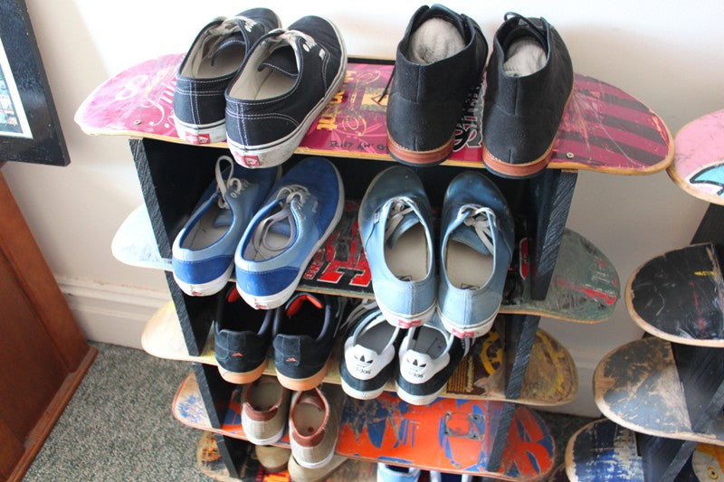 Skateboards stacked to make a shoe rack