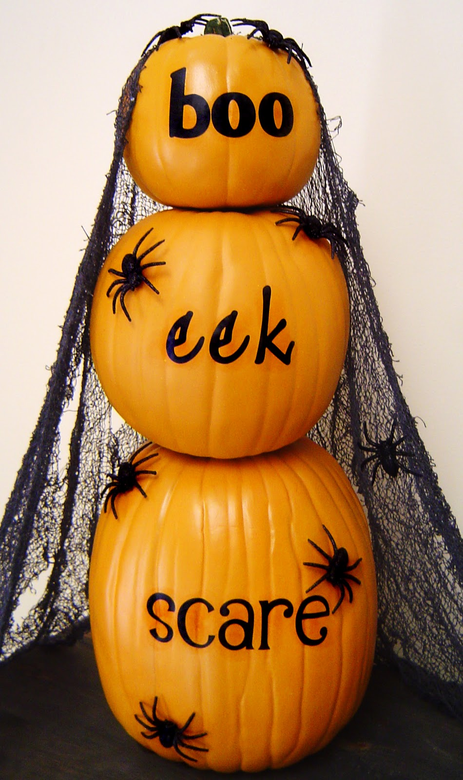Three pumpkins stacked on top of each, with boo, eel and scare written on them