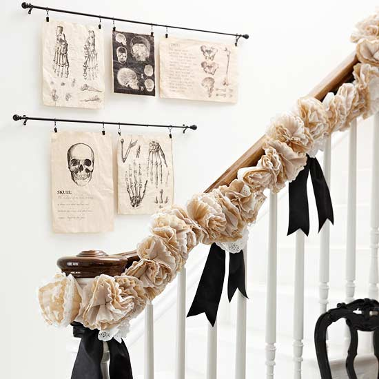 White staircase with wooden banister, with ruffled beige and black decorations and skeleton illustrations on the wall