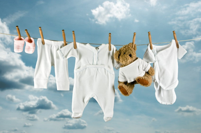 Childrens white clothing and teddy bear hung on a washing line
