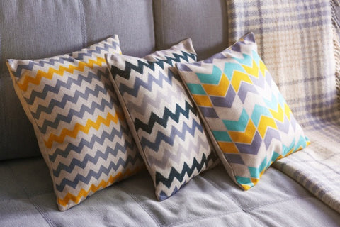 Geometric Cushions In Grey, Yellow, Teal And Black On A Grey Sofa