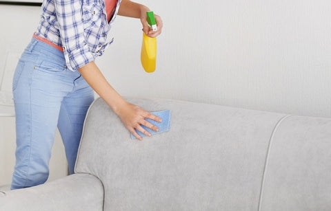 Grey Sofa Being Cleaned With Cloth And Cleaning Spray