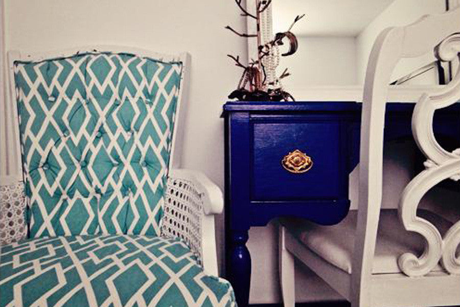 Dark cobalt blue dressing table, with a white framed mirror on top, next to a white and aqua chair