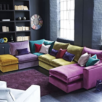 Urban living room with dark grey painted bricks and corner sofa in different colours
