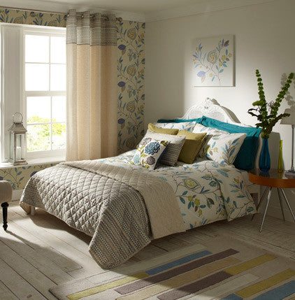 Cream and beige bedroom with cream bedding that has a floral pattern on it in light green and teal