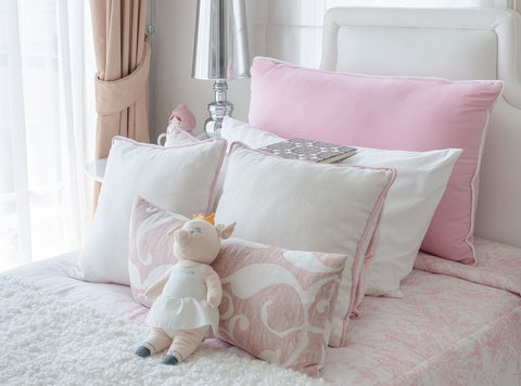 Pink And White Cushions Neatly Stacked On A Made Bed