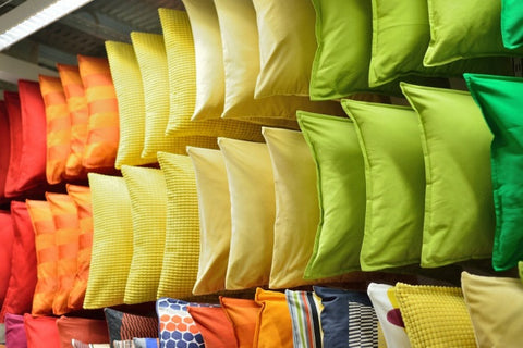 Different Shades Of Cushions Stacked On A Shelf Like A Rainbow