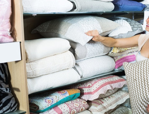 Woman Taking Cushions Of A Shelf In A Bedding Shop