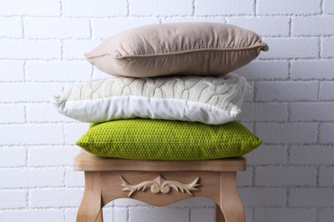 Stack Of Three Cushions On A Wooden Table
