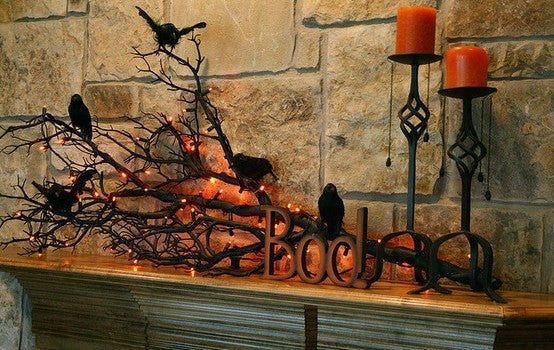 Black tree branch on a wooden fireplace, with model ravens on the branches