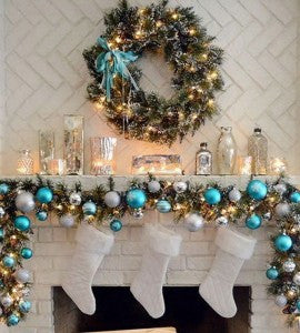 Garland and Christmas wreathe hung on a fireplace with silver and light blue baubles