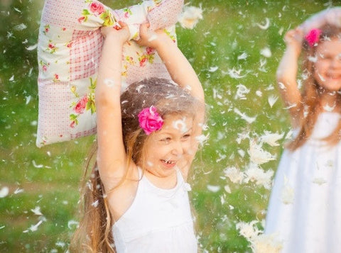 Feathers Everywhere As Two Young Girls Have A Playful Pillow Fight