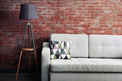 Funky Brick Wall, Black Tripod Floor Lamp And Grey Sofa