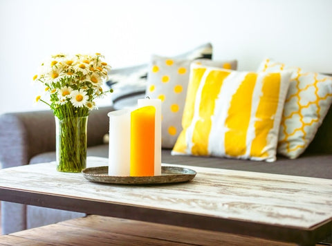 Daisies And Candles On A Coffee Table In Front Of Bright Yellow And Grey Cushions