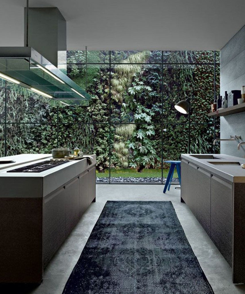 Dark Black And Grey Kitchen With Beautiful Large Floor To Ceiling Window Overlooking Garden Trees And Hedges