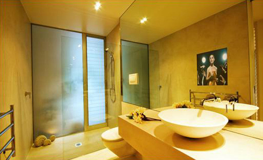 Gold and cream bathroom with smart mirror containing a TV screen