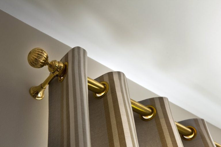 Brown striped curtains on a golden curtain pole