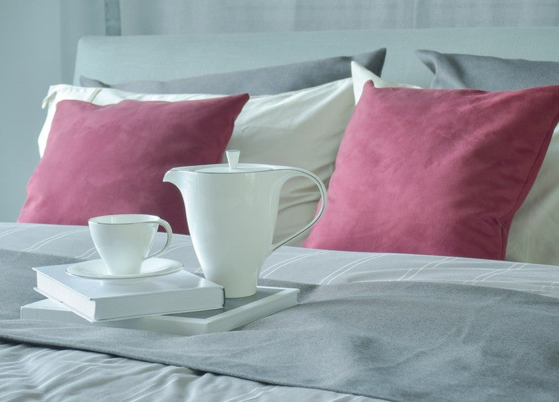 Tea Cup And Books Sitting On A Grey Bed Runner, With Maroon Cushions At The Head Of The Bed