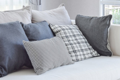 Grey, Blue And Checked Cushions On A White Sofa