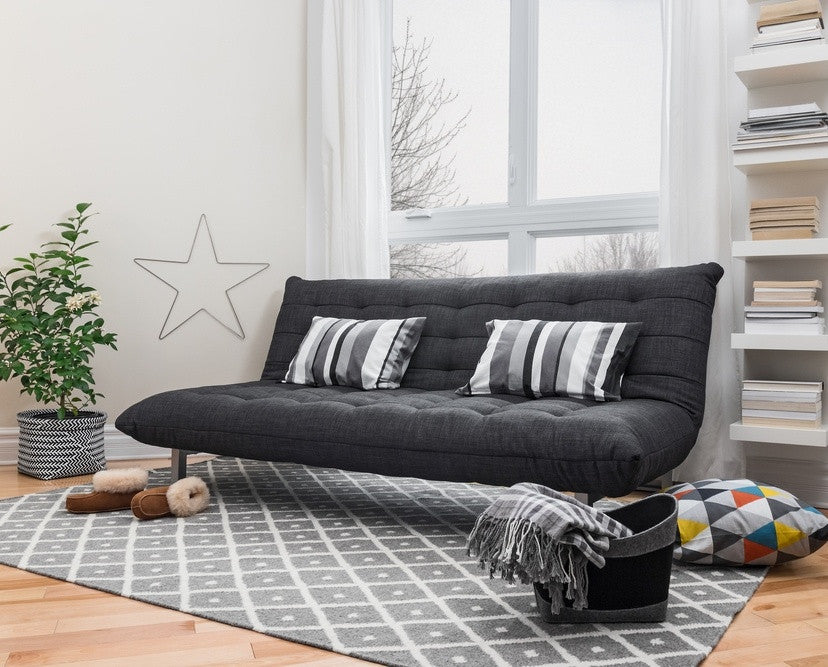 Black Fold Out Bed With Grey Striped Cushions On A Grey Geometric Rug