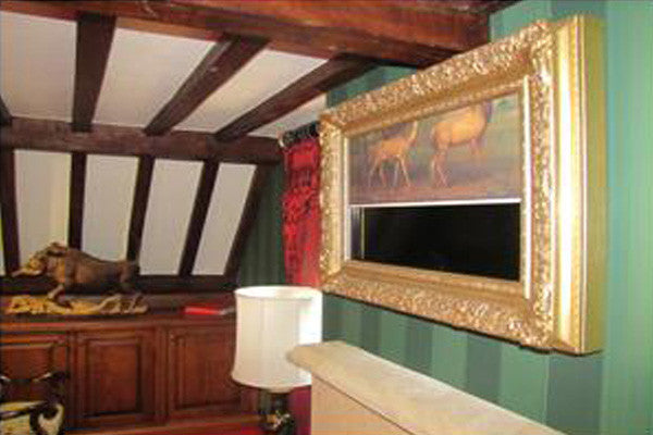 Traditional wood beam room with wooden furniture and a gold frame with concealed TV screen, behind a retractable picture canvas