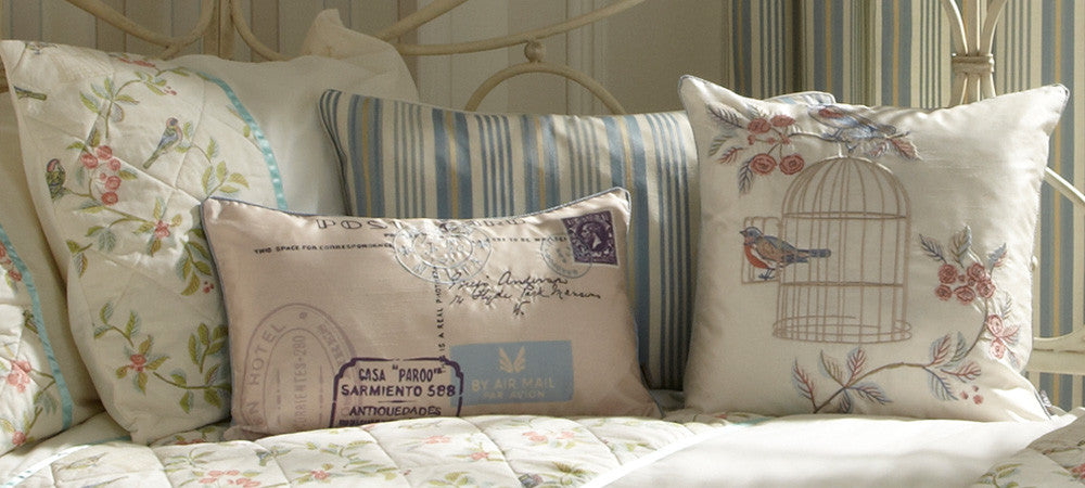 Close up of different cream cushions on a metal frame bed