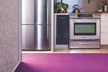 Purple rug in a modern kitchen, looking at fridge and cooker
