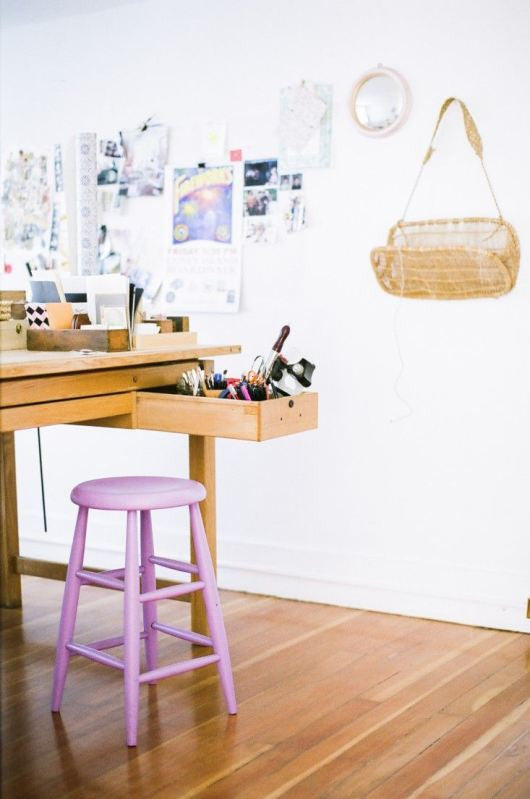 White art studio with wooden desk and pink stool