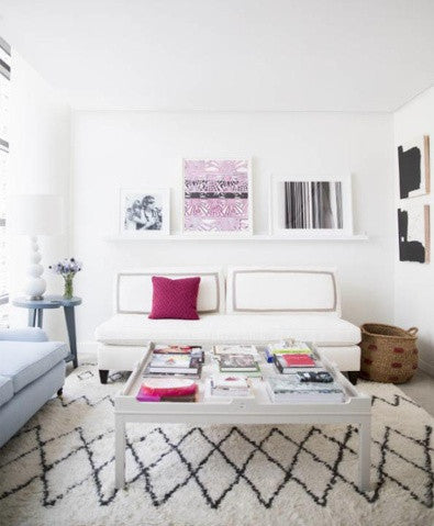 White living space with black and white rug, and similar artwork on the wall
