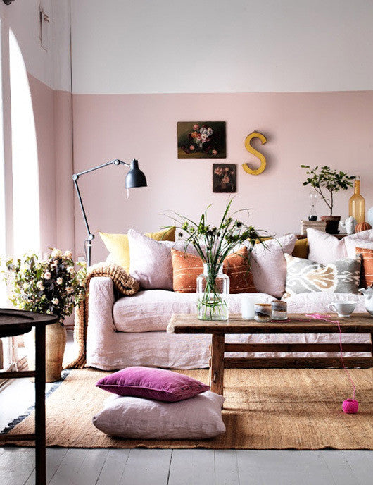 A light pink living room with matching sofa and long wooden coffee table