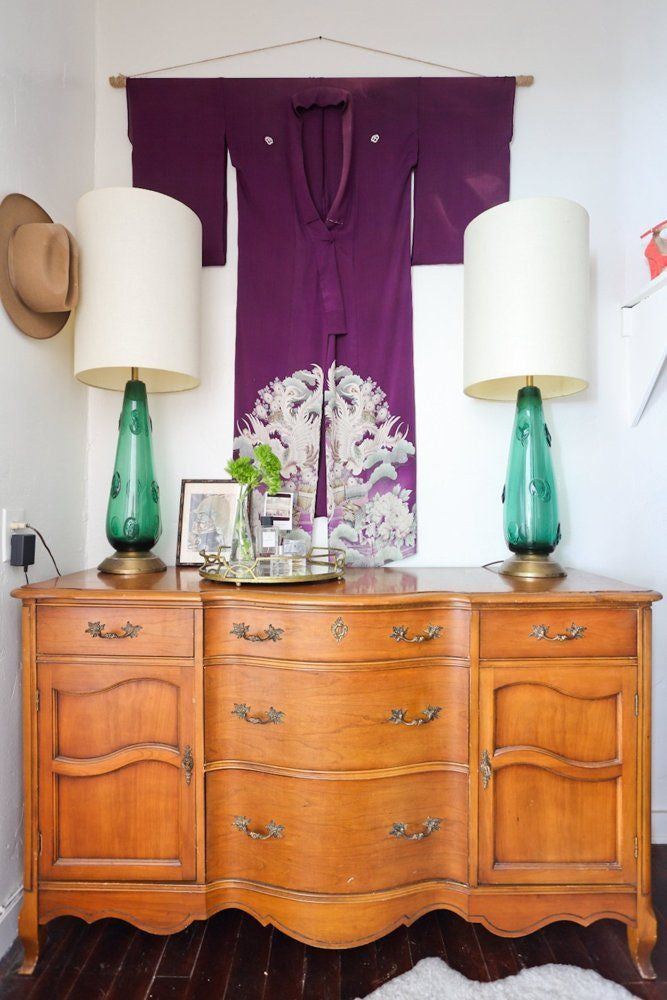 White alcove with an antique wooden dressing table adorned with two green glass lamps