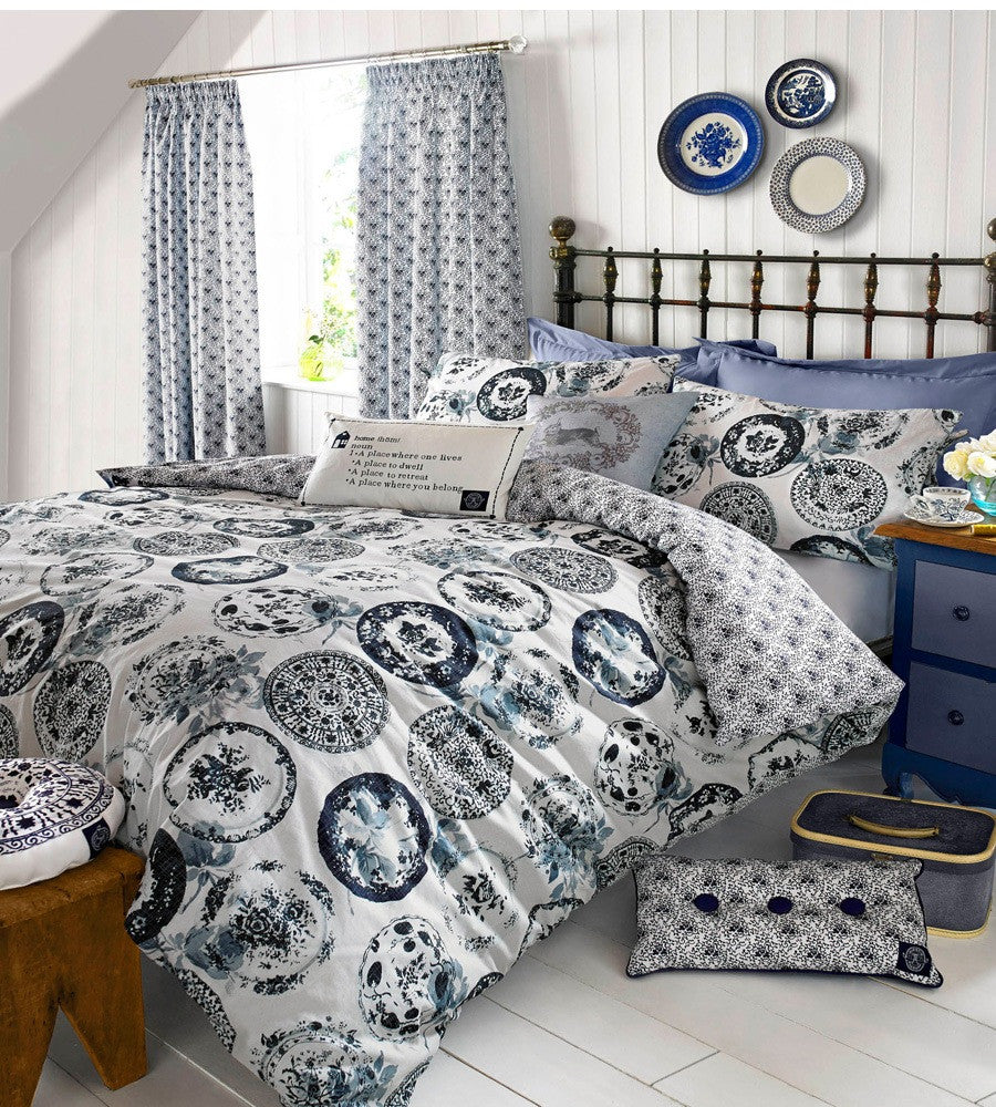 White bedding with blue circle design that look like different patterned plates or circular rubber stamps
