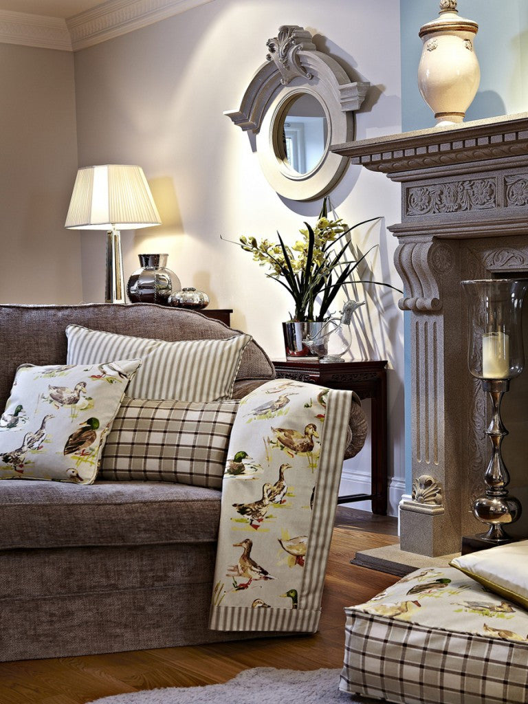 Cream living room with brown sofa and brown fireplace mantle, and mallard duck fabric draped over the sofa