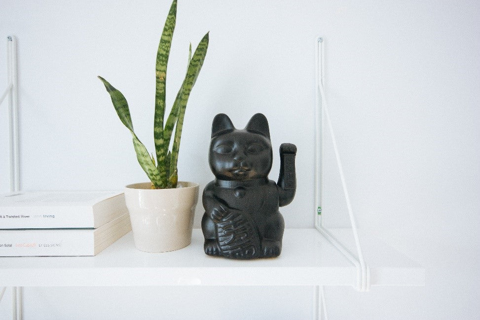 Chinese style black waving cat ornament on a shelf next to a plant pot