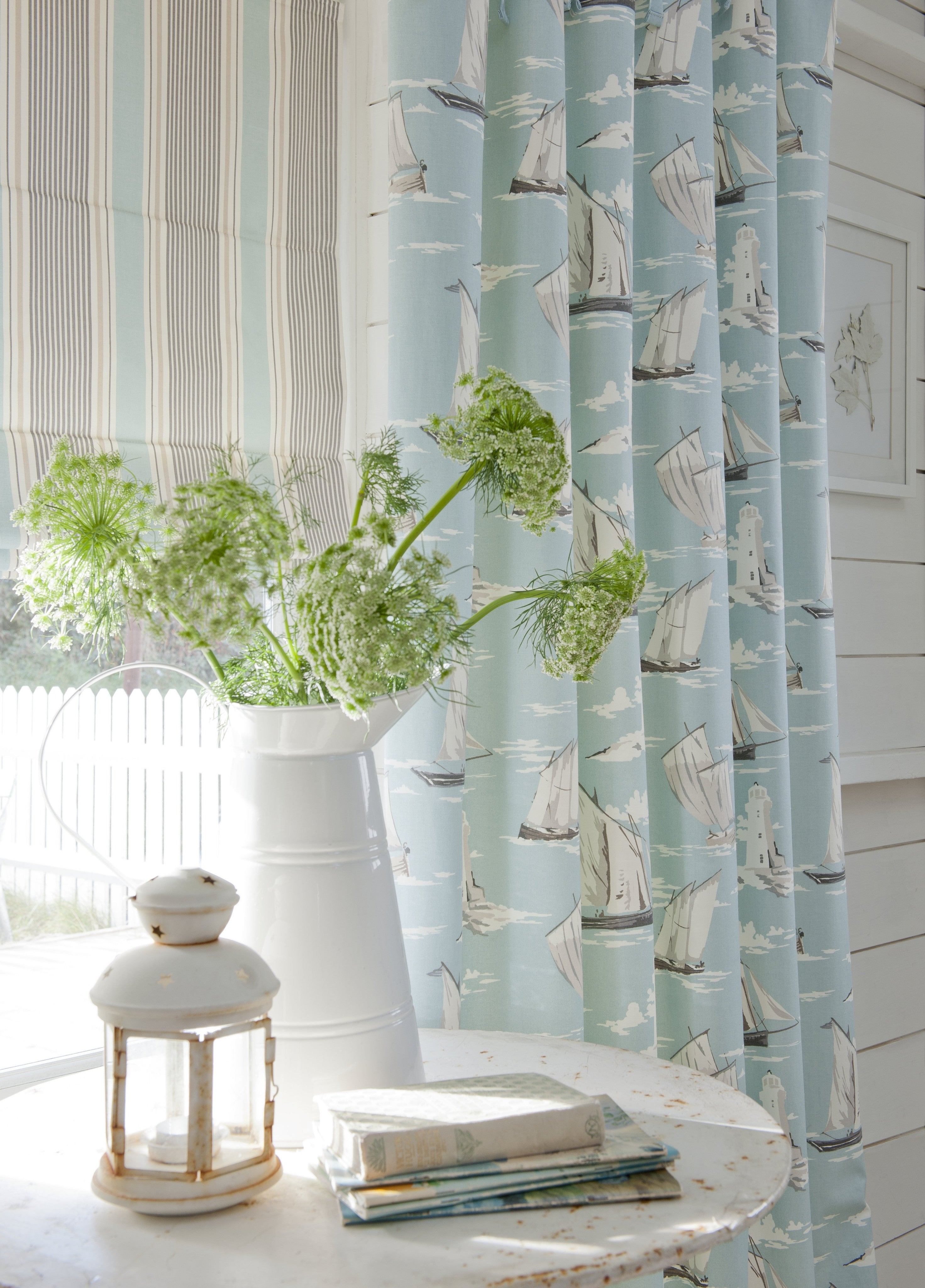 Sail Boats On A Light Blue Curtains, Striped Roman Blind And White Road Table With Flowers