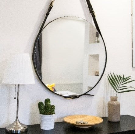 Large circular mirror hanging from a strap, above a black storage unit