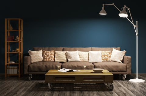Lamp With Two Heads And Brown Sofa Dimly Lit In Front Of Dark Blue Wall