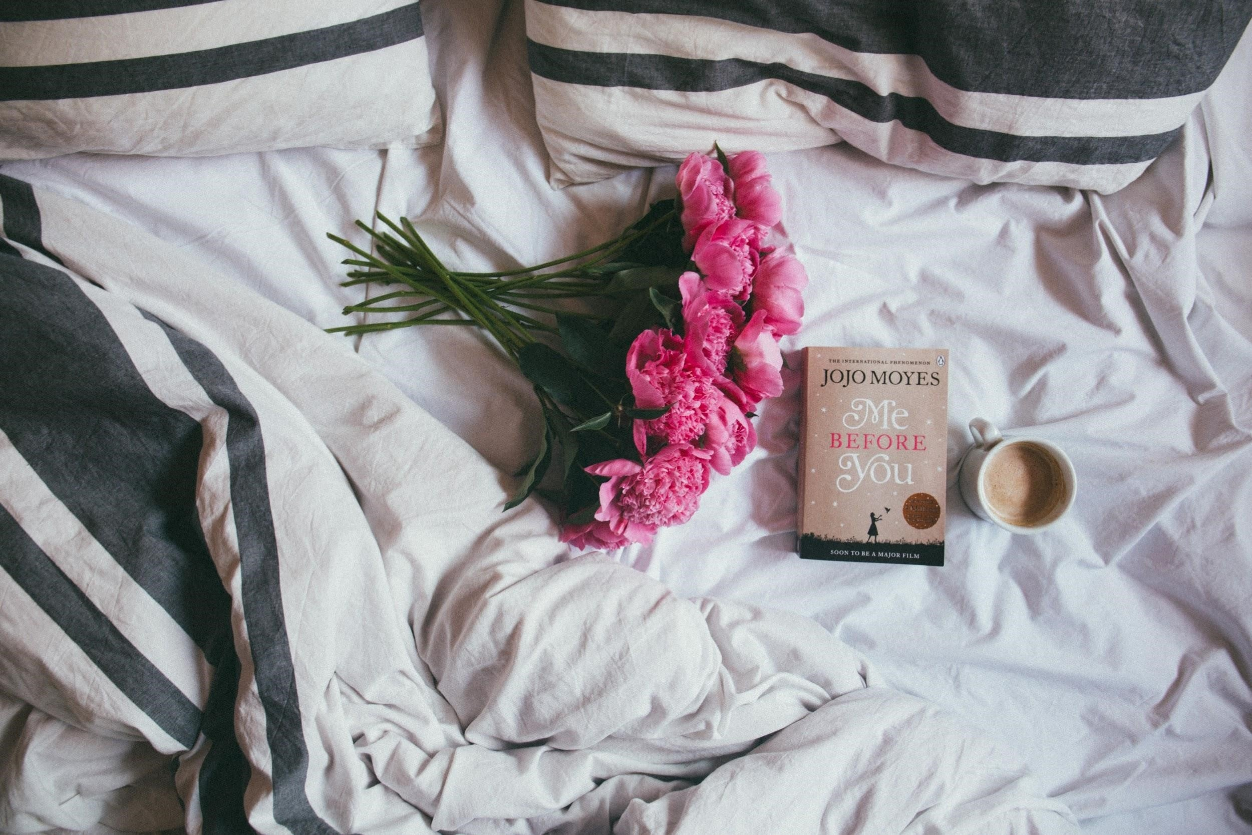 Flowers, A Book And A Coffee Cup On An Unmade Bed
