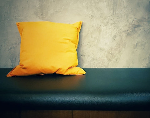 Square Yellow Cushion On Black Leather Bench
