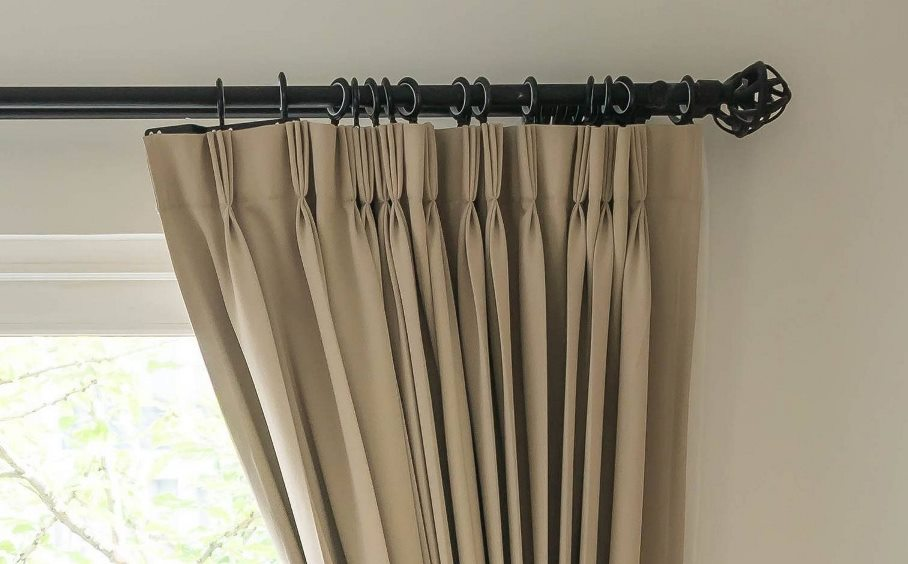 Black curtain pole and beige curtains