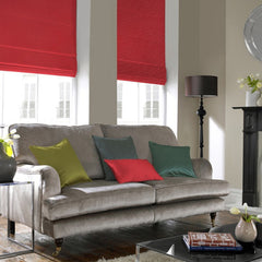 Two red blinds behind a grey sofa with bright cushions