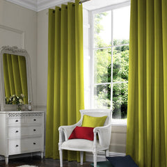Light green eyelet curtains in a window