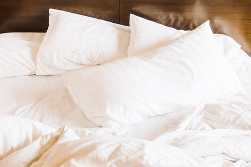 Unmade bed with white pillows, sheets and linen