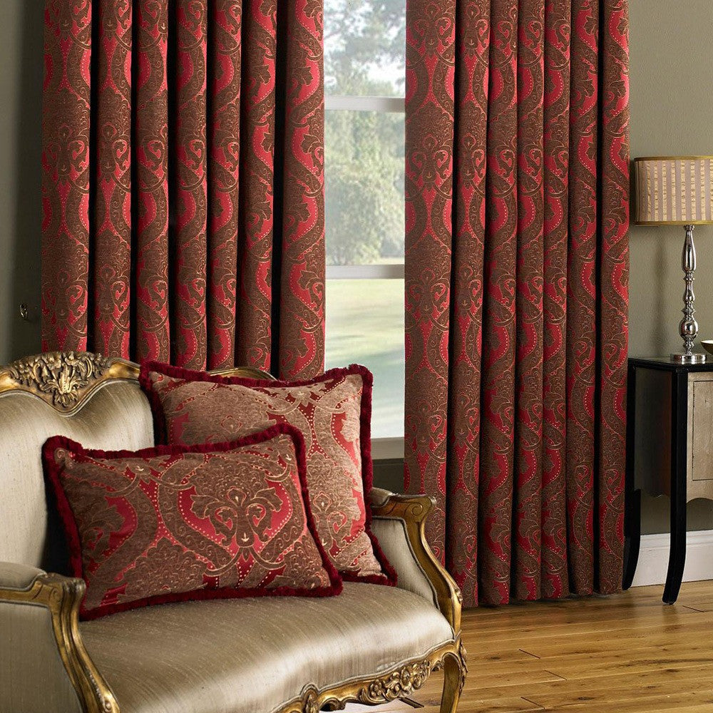 Burgundy and red damask curtains hung at a window
