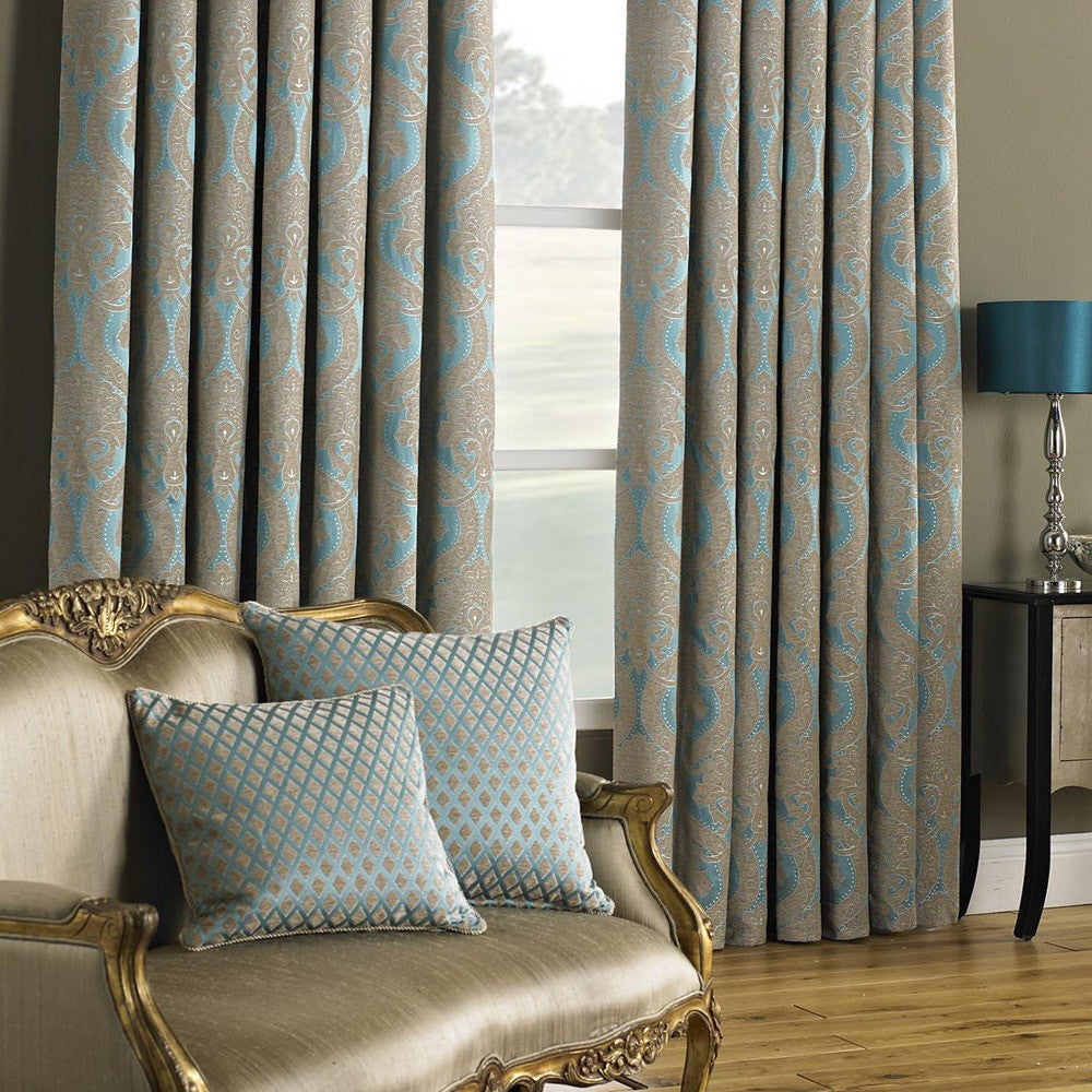Beige and turquoise damask curtains hung at a window