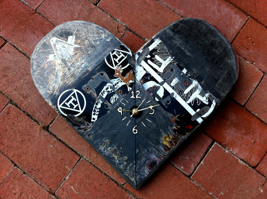 Two pieces of a skateboard joined to make a heart shaped clock