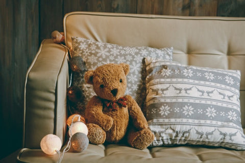 Traditional Teddy Bear On Beige Sofa, Next to Grey Festive Cushions