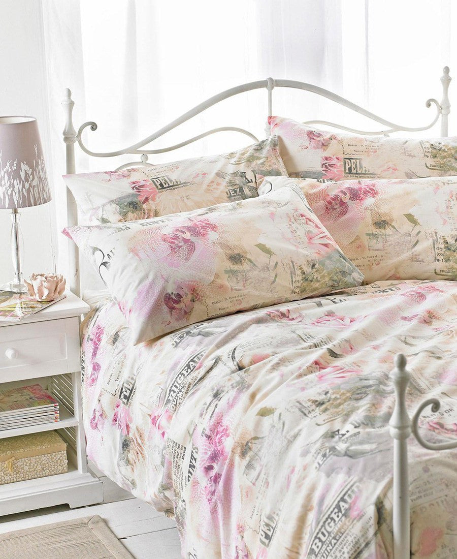 Cream and light pink floral bedding on a white metal bed frame