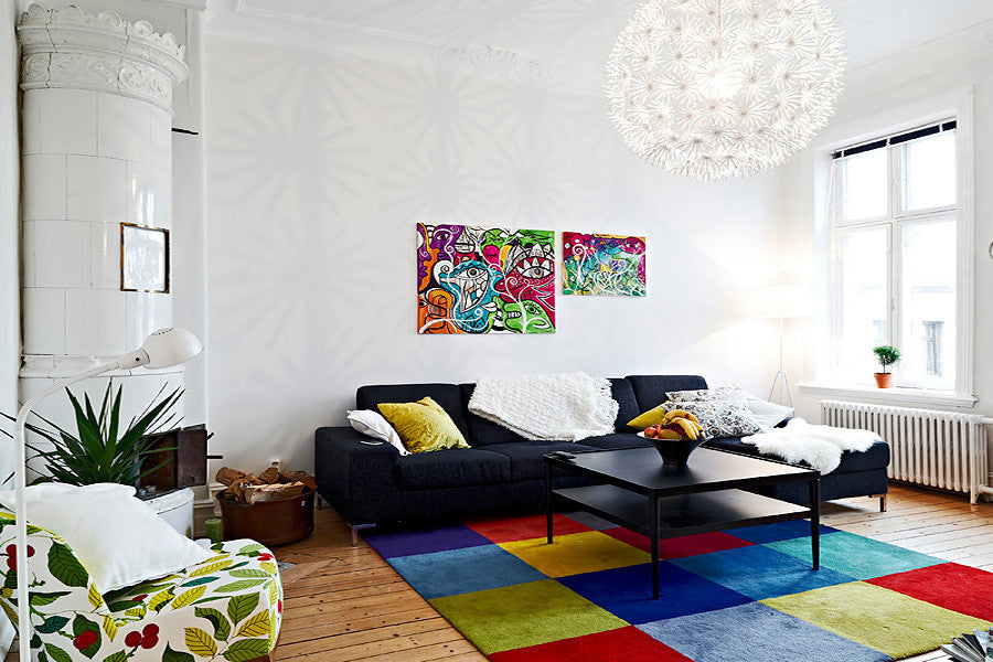 A large white lving space with dark blue or black sofa on a multicoloured patchwork rug