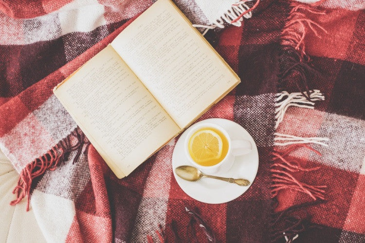A Book And Hot Lemon Drink On Top Of A Red Tartan Throw